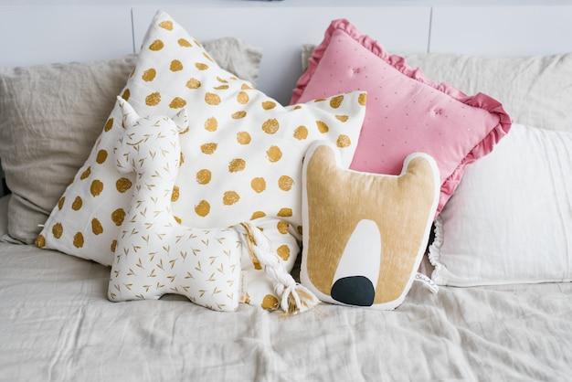 Kussens in de vorm van een eenhoorn en een vos, en roze en wit met gele erwten op het bed
