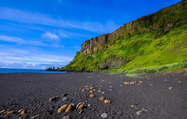 Kust in de buurt van een met gras begroeide heuvel en een klif met een blauwe lucht op de achtergrond
