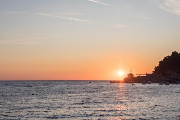 Kust tijdens zonsondergang. donkere zee oppervlak met zon reflectie