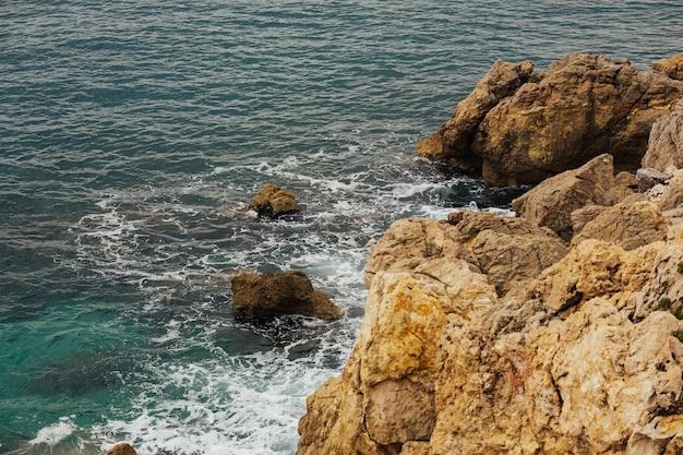 Kust van de middellandse zee met oranje rotsen en azuur helder transparant water.