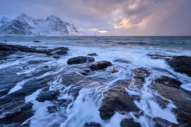 Kust van de noorse zee op rotsachtige kust in fjord op zonsondergang
