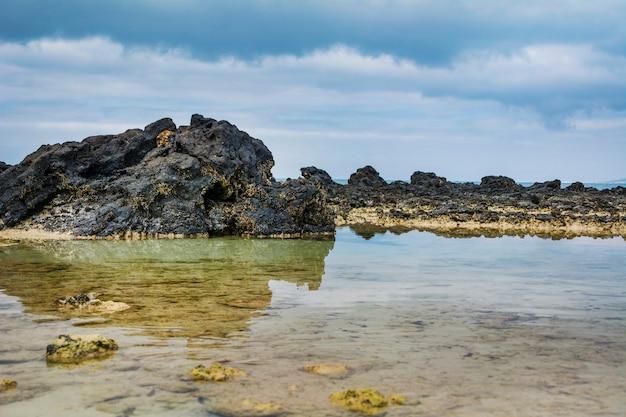 Kustlandschap, rotsen en lucht weerspiegeld in het water.