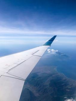 Kustlijnmening van vliegtuigvenster op zonnige dag. vliegen en reizen concept