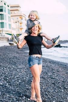 Kustplaats met mooie moeder en zoon die op zijn rug glimlachen en samen lachen aantrekkelijke blonde familie die geniet van de vrijetijdsbesteding in de buitenlucht en een gezonde levensstijl. vrolijke mensen bij de b