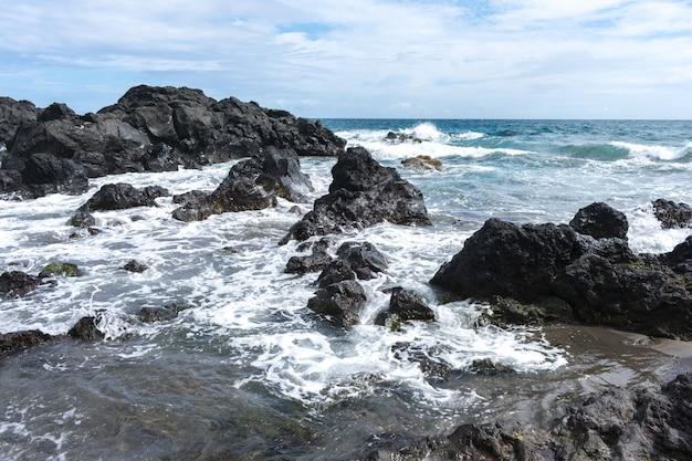 Kustrotsen in de azoren. golven die op basaltrotsen bespatten