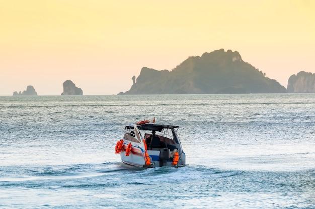Kustwachtmotorboot vaart vanaf de kust zonsonderganghemel en bergen man bestuurt een reddingsschip