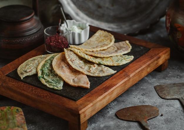 Kutab-variëteiten op een steakboard met sumakh en yoghurt.