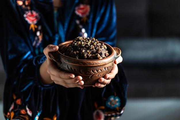 Kutia vrouw in slavische jurk met kom pap gemaakt van tarwekorrels, maanzaad, noten, rozijnen en honing