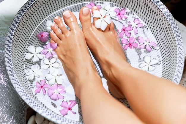 Kuur en product voor vrouwenvoeten. voetbad in kom met tropische bloemen, thailand. gezond concept.
