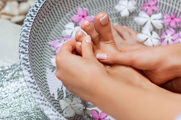 Kuur en product voor vrouwenvoeten voetbad in kom met tropische bloemen