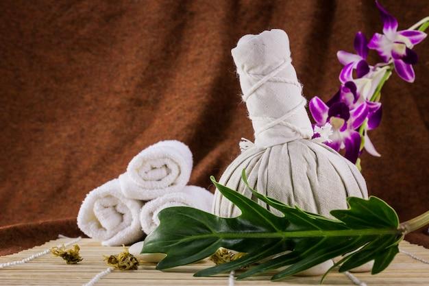 Kuuroord kruiden samenpersende bal met kaarsen en orchidee op bruin.