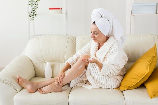 Kuuroord thuis vrouw hydrateert haar benen met body milk long shot