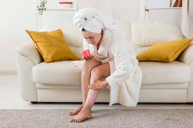 Kuuroord thuis vrouw hydrateert haar benen met crème