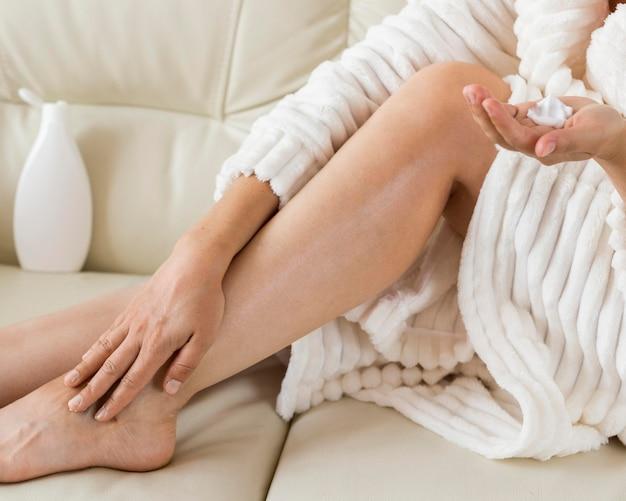 Kuuroord thuis vrouw hydrateert haar benen met lichaamsmelk