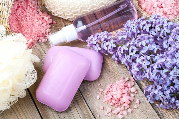Kuuroordachtergrond met tot bloei komende lilac bloemen en fles aromaolie of bloemhydrolaat, kosmetische zeep