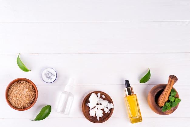 Kuuroordachtergrond met voorbereidings met de hand gemaakte natuurlijke cosmetischee producten op wit hout