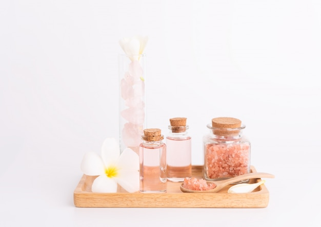 Kuuroordbehandeling met roze vloeibare zeep, roze zout, stenen en plumeria-bloem op houten dienblad over wit