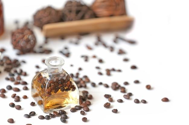 Kuuroordconcept. aroma olie en koffiebonen op wit oppervlak
