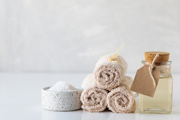 Kuuroordconcept met olie, met badzout en handdoeken op een witte achtergrond. stilleven met spa en wellness. kopieer ruimte.