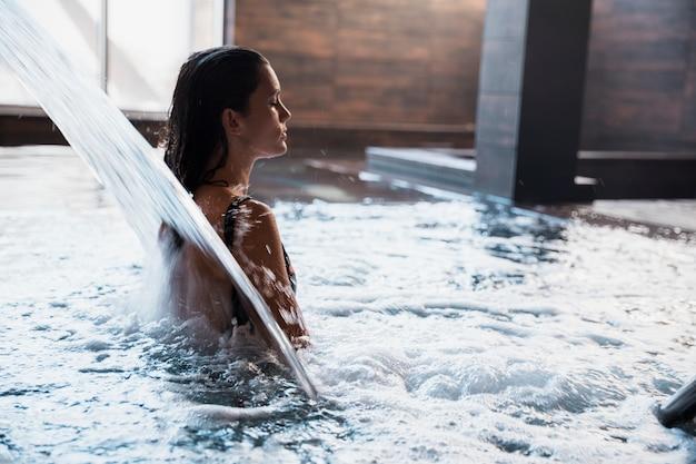 Kuuroordconcept met vrouw het ontspannen in water