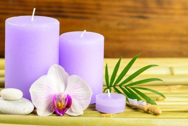 Kuuroordhanddoeken, kaars en orchidee op bamboe