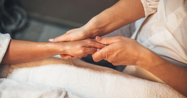 Kuuroordmedewerker die de hand van de klant met speciale lotion masseert tijdens een handmassagesessie in de kuuroordsalon