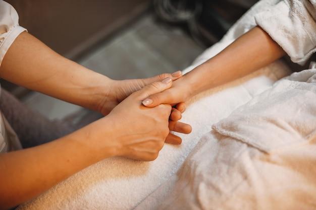 Kuuroordmedewerker die de hand van de patiënt masseert