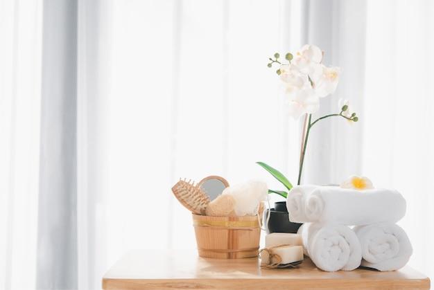 Kuuroordproducten met witte handdoeken, zeep, luffa-scrub, kam en mooie orchideebloem in schone witte ruimte