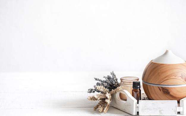 Kuuroordsamenstelling met aromaverspreider en natuurlijke het exemplaarruimteachtergrond van de lavendelolie