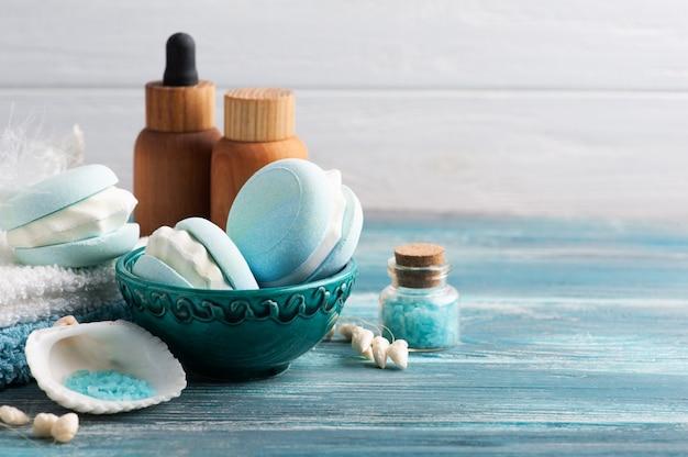 Kuuroordsamenstelling met de makaron van de badbom en droge bloemen op rustieke achtergrond. essentiële olie en zout. schoonheidsbehandeling en ontspannen