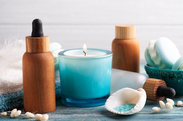 Kuuroordsamenstelling met etherische olie en zout en droge bloemen op rustieke achtergrond. schoonheidsbehandeling en ontspannen