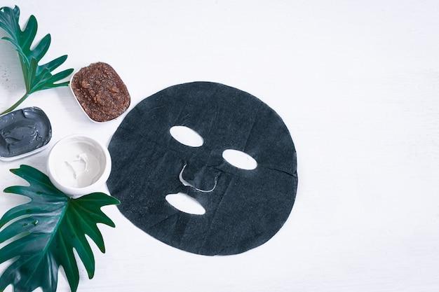 Kuuroordsamenstelling met gezichtsverzorgingsproducten met een zwart masker en bladeren. het moderne concept van spa- en schoonheidsproducten.