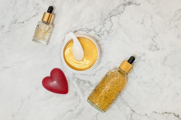 Kuuroordschoonheidsmiddelen op marmeren achtergrond. schoonheid blogger. copyspace.beauty huidverzorgingsproducten. olie, crème, serum, hydrogel gouden cosmetische ooglapje.