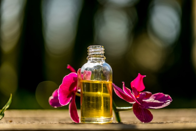 Kuuroordstilleven met etherische oliën en orchidee op bokehachtergrond.