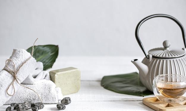 Kuuroordstilleven met huidverzorgingsproducten voor gezicht en lichaam en thee.