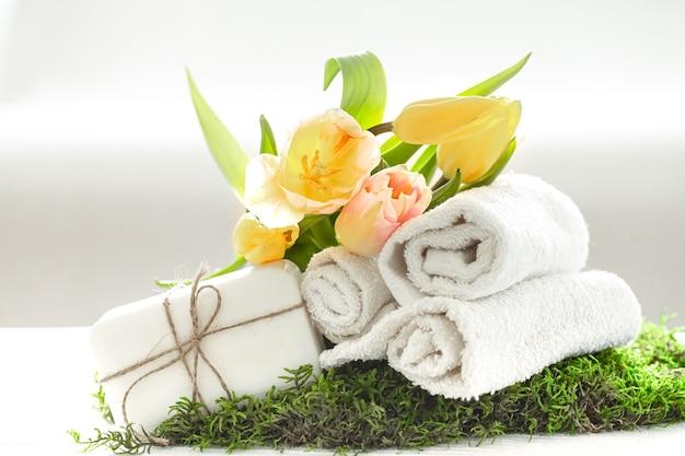 Kuuroordstilleven met natuurlijke zeep, handdoeken en gele tulpen op een lichte vage ruimte als achtergrondkopie.