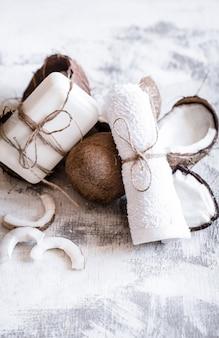 Kuuroordstilleven van organische schoonheidsmiddelen met kokosnoten op een lichte houten achtergrond, het concept van de lichaamsverzorging