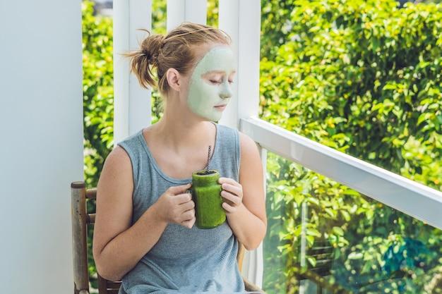 Kuuroordvrouw die gezichts groen kleimasker toepassen. schoonheidsbehandelingen. verse groene smoothie met banaan en