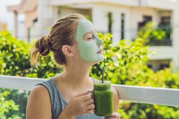Kuuroordvrouw die gezichts groene kleimasker schoonheidsbehandelingen verse groene smoothie met banaan toepassen en