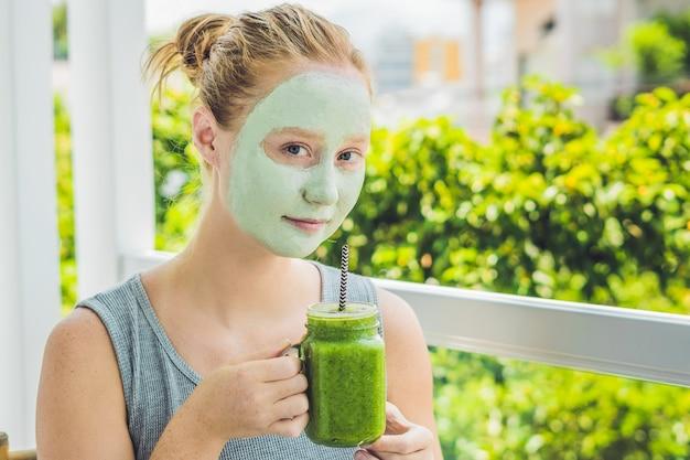 Kuuroordvrouw die gezichts groene kleimasker schoonheidsbehandelingen verse groene smoothie met banaan toepassen