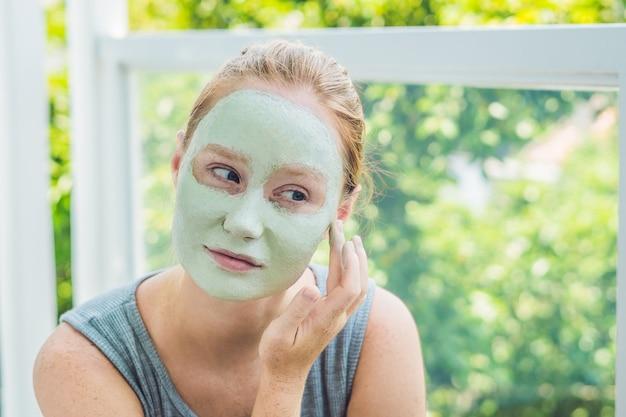 Kuuroordvrouw die gezichts groene kleimasker toepassen de close-upportret van de schoonheidsbehandelingen van mooi meisje Premium Foto