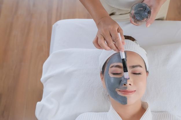 Kuuroordvrouw die gezichtskleimasker toepassen. schoonheidsbehandelingen.