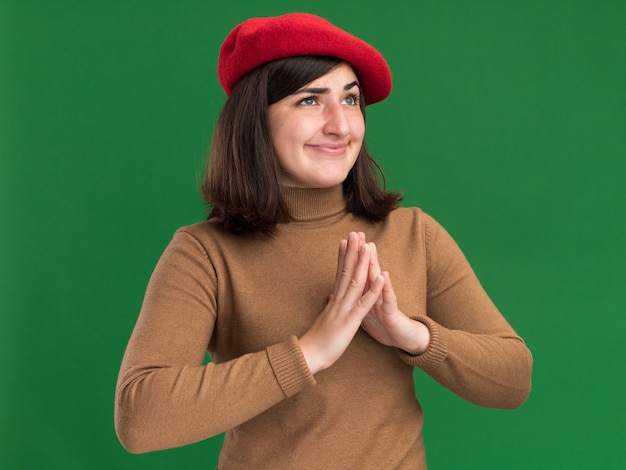 Kwaad vrolijk jong vrij kaukasisch meisje met barethoed houdt handen bij elkaar en kijkt naar kant op groen