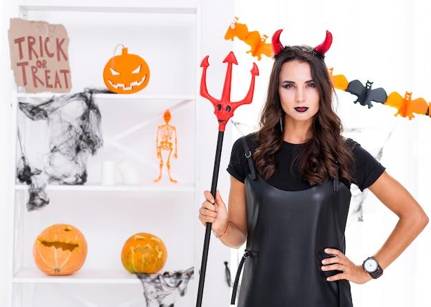 Kwade vrouw met drietand poseren voor halloween