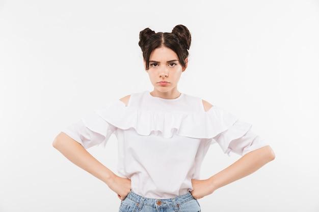 Kwalijk meisje met dubbele broodjes kapsel fronsen en staan met gevouwen armen, geïsoleerd op wit in de studio