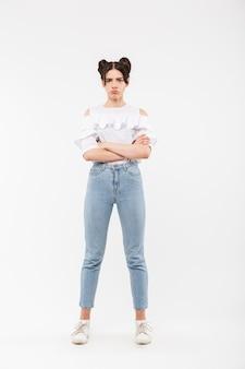 Kwalijk meisje met dubbele broodjes kapsel fronsen en staan met gevouwen armen, geïsoleerd op wit