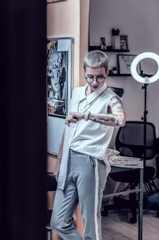 Kwalitatieve tatoeages. blonde kortharige buitengewone vrouw die haar horloge observeert terwijl ze op de volgende klant wacht