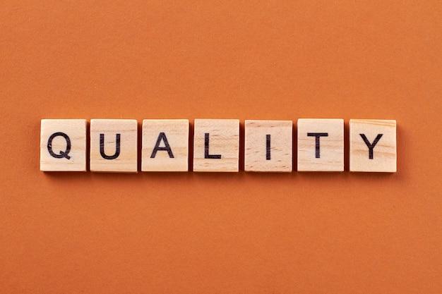 Kwaliteitsborging concept. kwaliteitsgarantie is belangrijk voor de klant. alfabetblokken met letters geïsoleerd op een oranje achtergrond.
