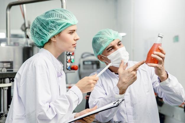 Kwaliteitscontrole en voedselveiligheidsteam inspecteren de productnorm in de productielijn van de voedsel- en drankfabriek.