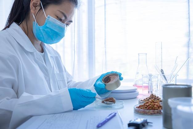 Kwaliteitscontrolepersoneel inspecteert de kwaliteit van ingeblikt voedsel voor huisdieren. fysieke kwaliteitscontrole. kwaliteitscontroleproces van de huisdiervoedingsindustrie.